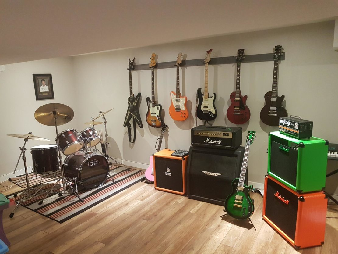 a music focused man cave, with drum kit, several big amps and multiple guitars hanging on the wall