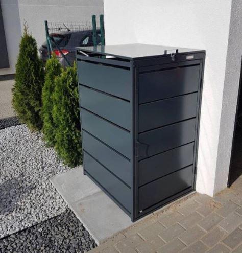 a narrow metal bin storage unit next to the driveway of a house