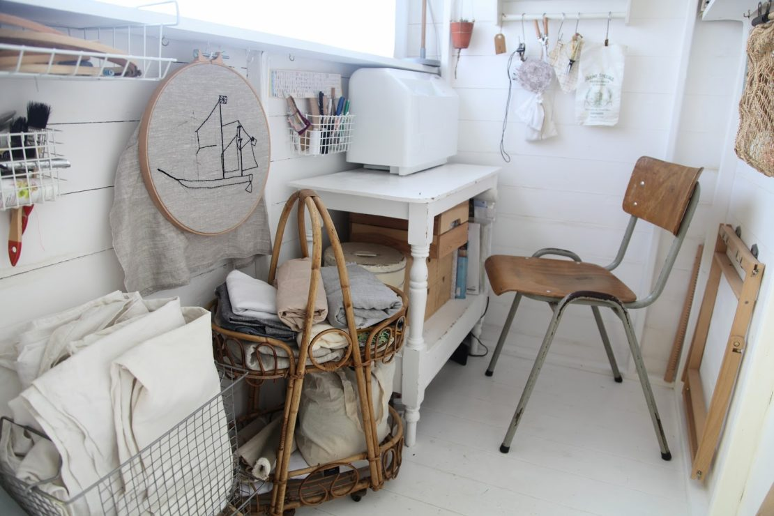 a narrow shed filled with sewing paraphernalia, including a cross stitch hoop and squares of fabric
