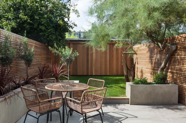 a neat garden with a patio and lawn, and a foldeed hammock hanging from a tree