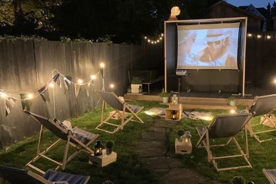 a night-time cinema set up with deck chairs and string lighting