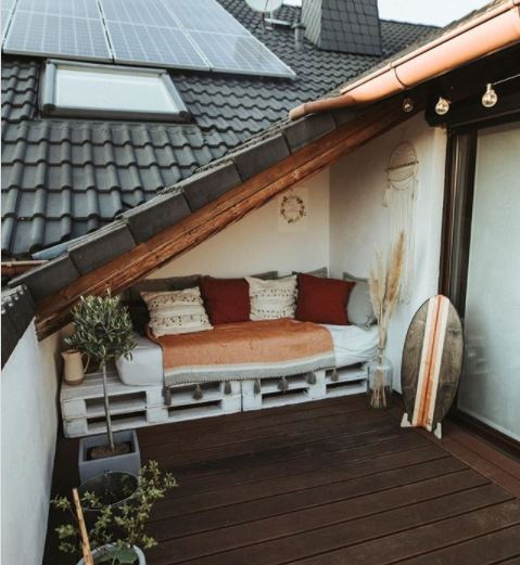 a pallet bench with cushions is fitted neatly under a low roof on a balcony