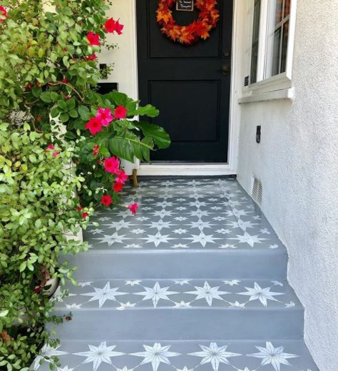 a path and front steps made from painted concrete that's been stencilled to look like tiles
