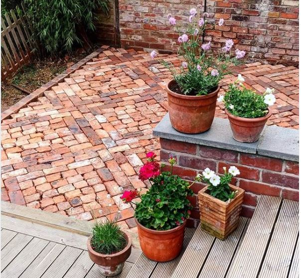 a patio made from vintage bricks next to a deck with potted plants