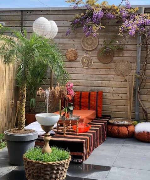 a patio with a low table covered in patterned cloth, and low pouffes and beanbags surrounding it