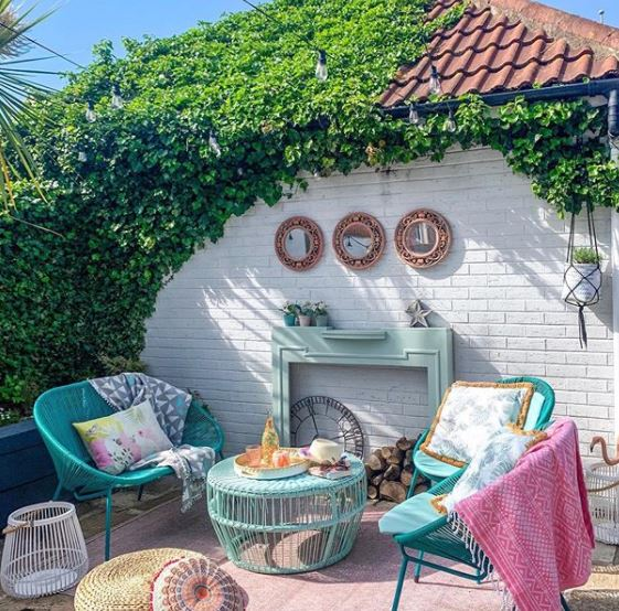 patio garden ideas with rug, chairs and coffee table, featuring a fireplace frame leaning against the rear wall