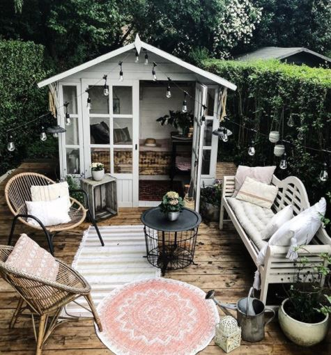 a pretty she shed with glass doors opens onto a deck with chairs, bench and outdoor rugsx
