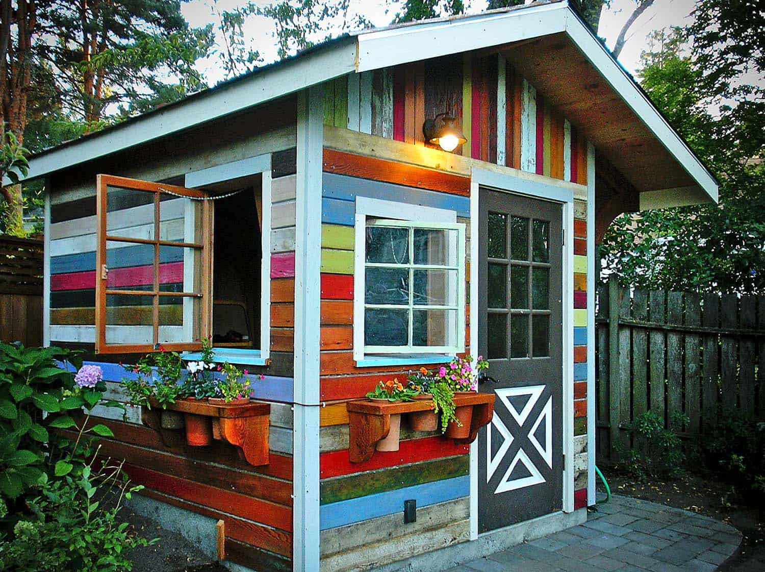 a quirky garden woman cave made from brightly coloured panels of reclaimed wood