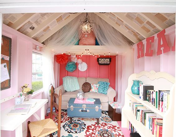 a quirky she shed interior, painted contrasting shades of pink and red, with a sofa, bookshelf and desk