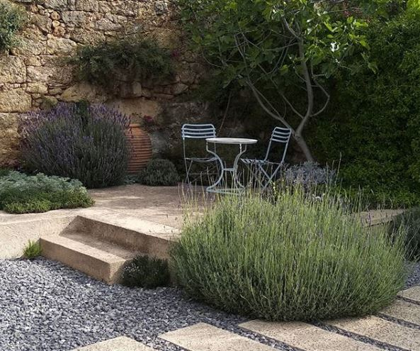 a raised stone patio with furniture, in a gravel garden with several huge lavender shrubs