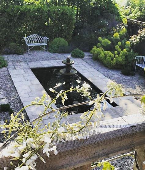 a rectangular pond with a fountain in the middle and white metal benches at the edge