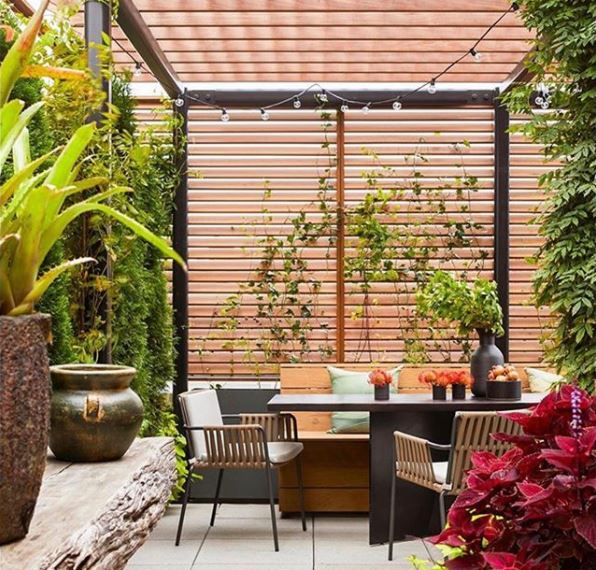 a rooftop garden with a dining table covered by a contemporary pergola