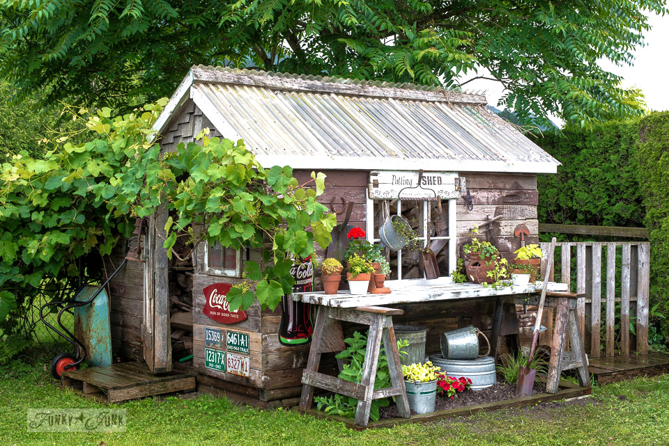 a rustic shed with workbench potting area outside and vintage signs as exterior decor