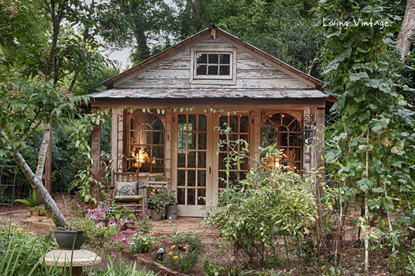 a rustic, weathered wooden shed with large windows and a covered porch