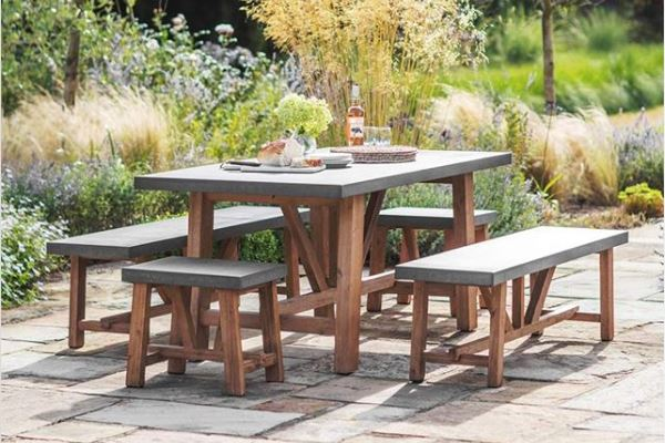 a set of benches and dining table with wooden frames and concrete tops on a rustic flagstone patio