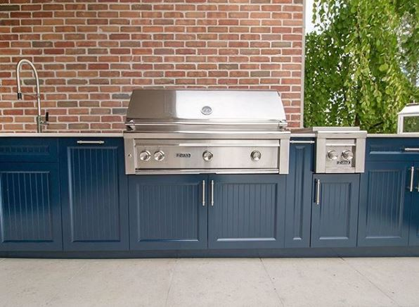 a shiny in-built grill in an outdoor kitchen with smart navy cupboards