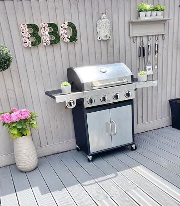 a sleek freestanding BBQ on a grey deck with pretty garden decorations