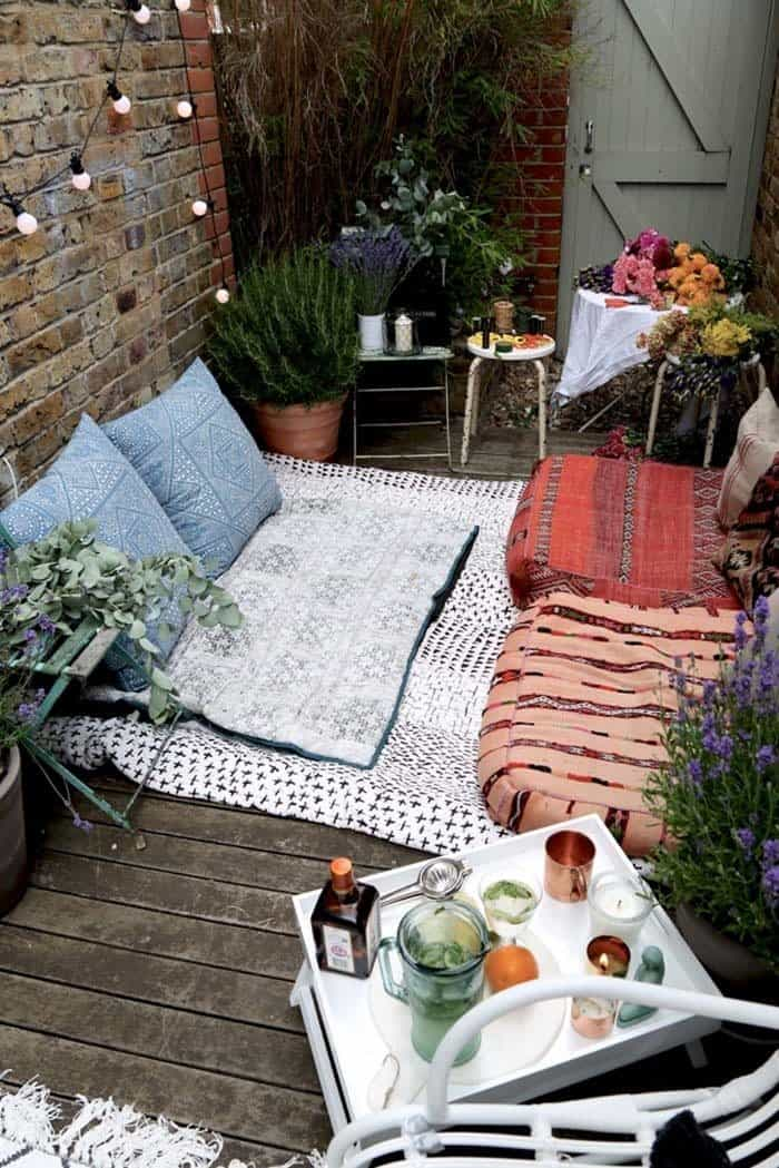 a small bohemian courtyard with blankets on the floor and large cushion seats