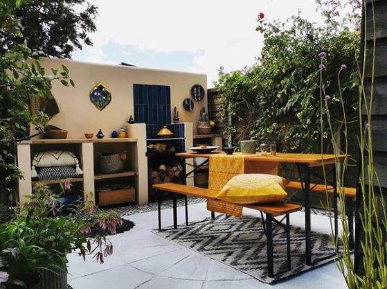 a small courtyard garden painted yellow, with a picnic table, rugs and cushions