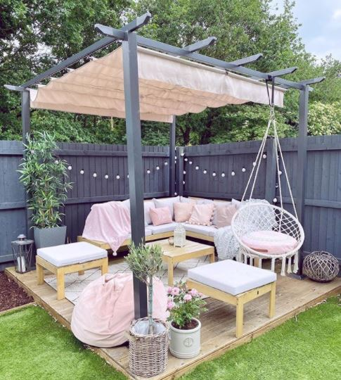 a small deck covered by a pergola, with a sofa, two stools and a hanging chair, all with matching white and pink cushions