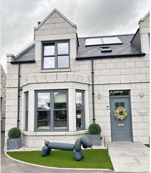 a small front garden covered with artificial grass with a large lawn concrete ornament shaped like a balloon animal