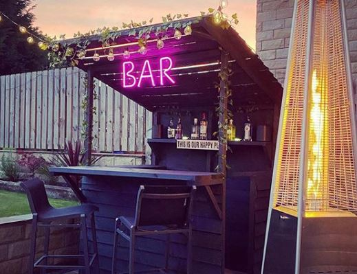 a small garden bar with pink LED neon light that reads BAR and a patio heater