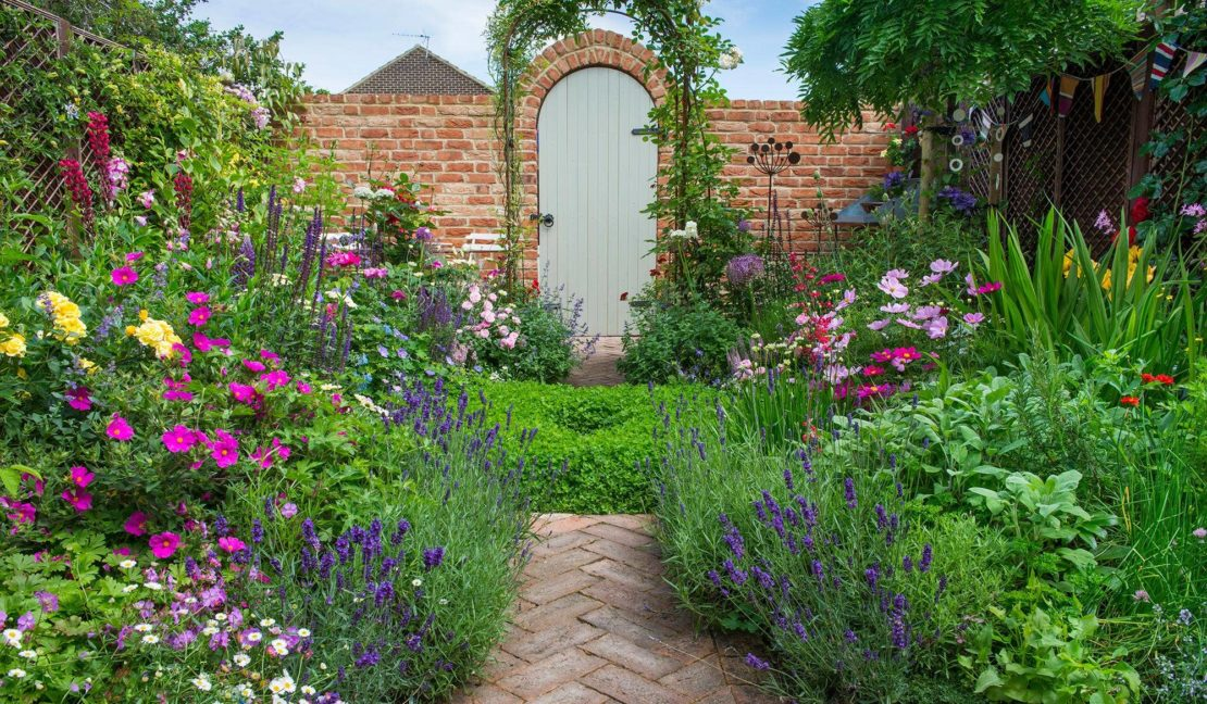 a small garden with overflowing flower beds and a brick path leading to a pretty gate at the end