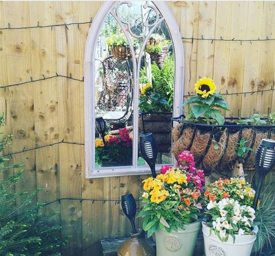 a small mirror shaped like a gothic window, reflecting colourful pots and flowers