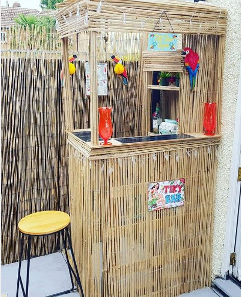 a small outdoor bar made from recyclet pallets, covered with bamboo matting to give it a tiki vibe.