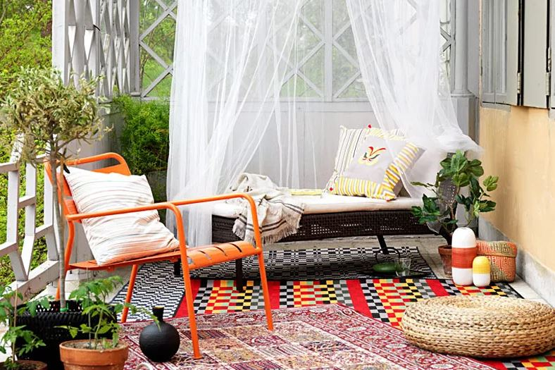 a small terrace with a bright orange chair, loud, clashing rugs and a day bed beneath a white net canopy