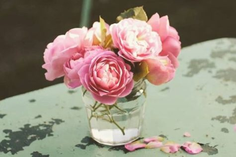 a small vase of freshly cut Boscobel roses, on a weathered tabletop