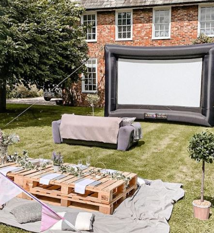 a sofa and pallet coffee tables in front of a large inflatable cinema screen