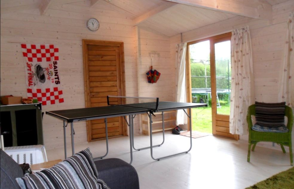 a spacious garden shed with a ping pong table in the middle