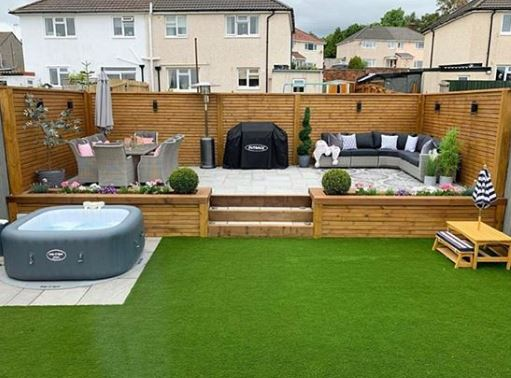 a split-level garden with a patio section on the upper level, and a picnic bench, inflatable hot tub and artificial lawn below