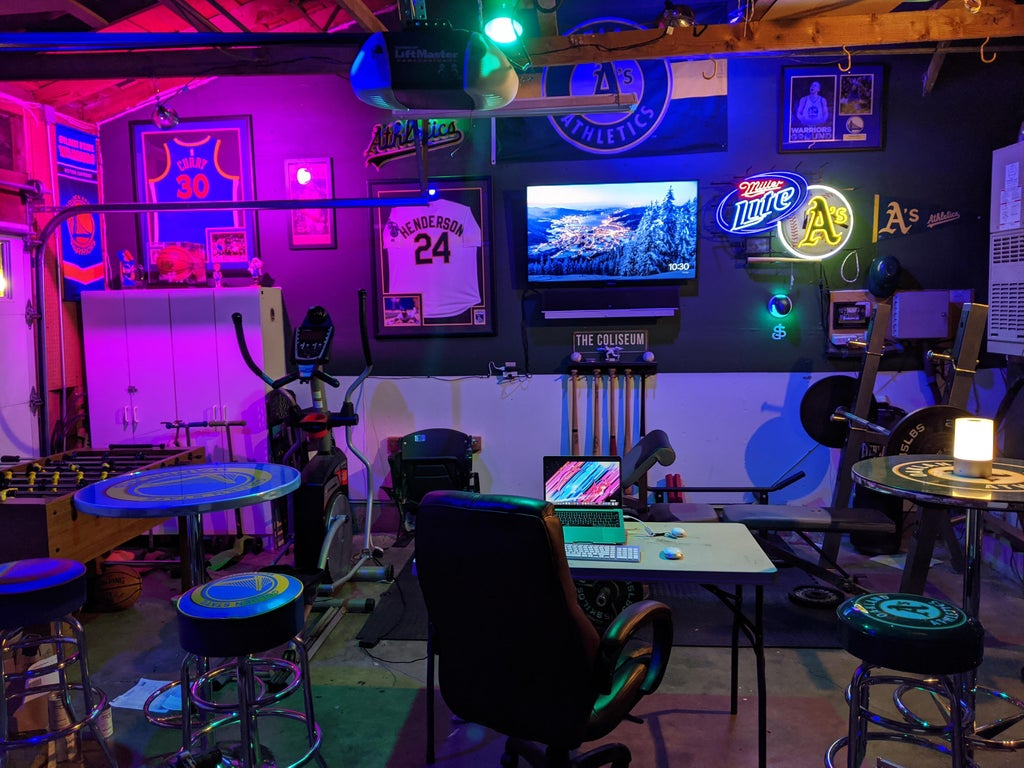 a sports-bar style man cave, with bar stools, gym equipment, neon lights and framed sports shirts