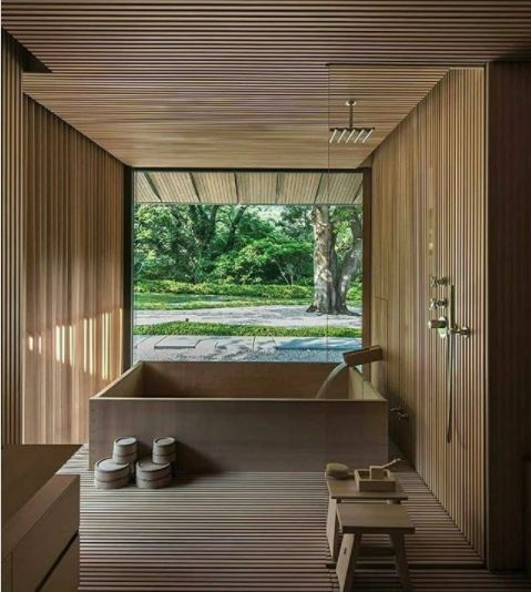 a square japanese style bath in a room with narrow wood panels and large windows that make it feel like it's outside
