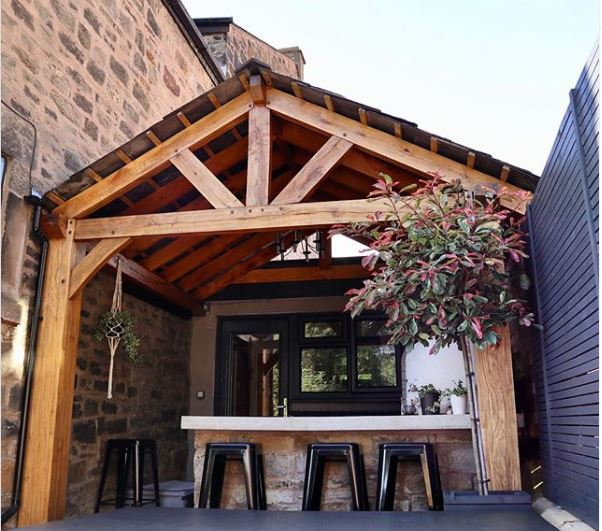 a sturdy lean-to extension with a stone bar and pizza oven underneath