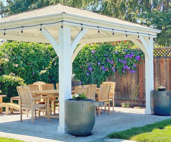 a sturdy white gazebo with a dining set beneath it and festoon lighting around the outside