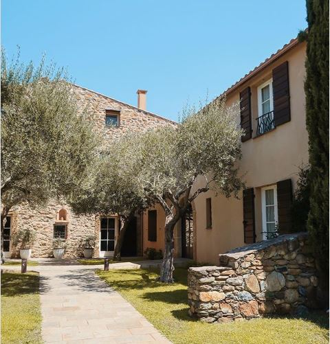 a sunny garden with olive trees, stone walls and a stone path leading throguh the centre