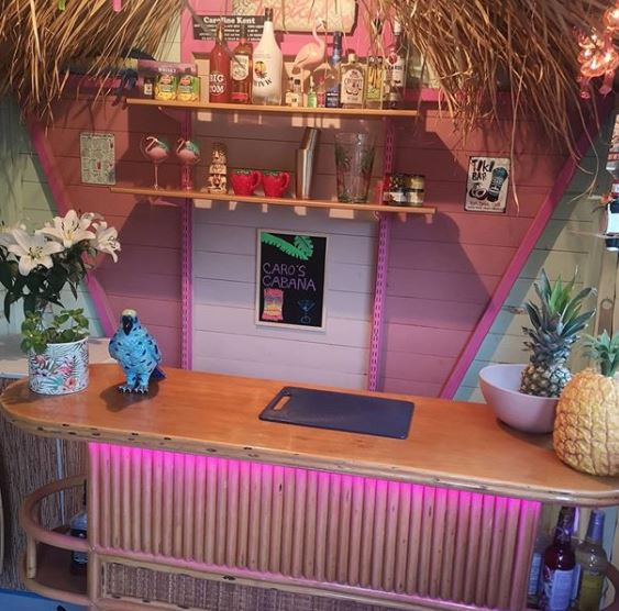 a tiki style shed bar with neon pink lights, kitschy decor and shelves filled with cocktail spirits