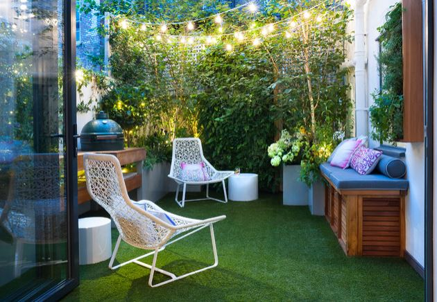 a tiny terrace with plants as fencing, string lights, slimine chairs, a storage bench and artificial grass