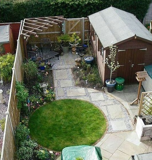a top-down view of a small garden with a carefulyl defined circular lawn