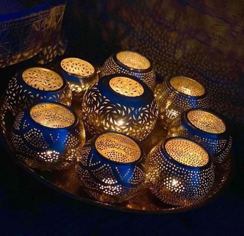 a tray of ornate silver tealight holders with little candles inside