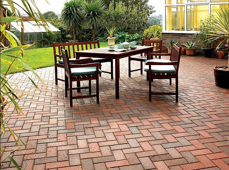 a very clean patio made from paving block in red and brown, laid in a herringbone pattern
