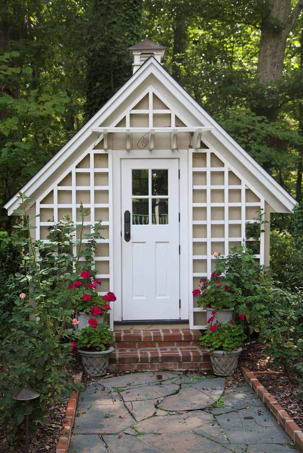 a very cute she shed with a trellis completely covering the front