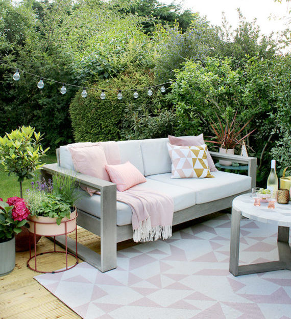 a white and grey outdoor sofa with pink cushions, on a pretty white and pink rug