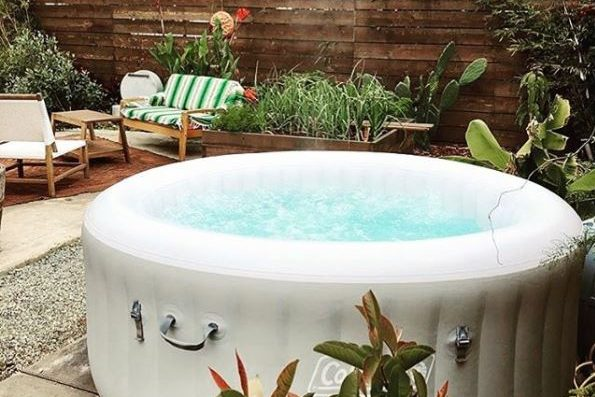 a white inflatable hot tub near a chic wooden sofa and chair set