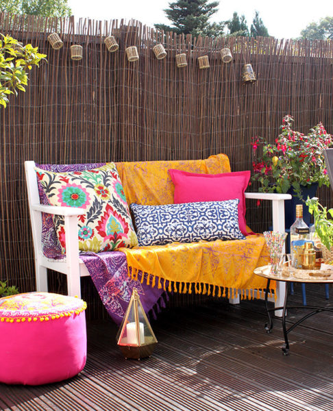 Moroccan themed garden ideas with a bench that has coordinated cushions in mustard yellow, hot pink, bright purple and deep blue