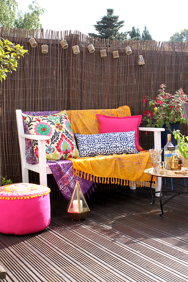 a white wooden bench with coordinated cushions in mustard yellow, hot pink, bright purple and deep blue