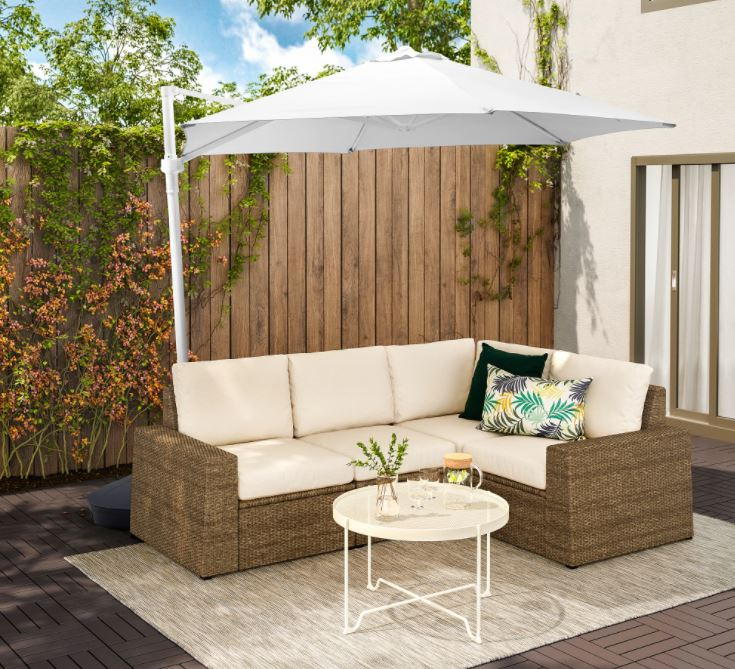 a wicker outdoor sofa and metal coffee table beneath a large white parasol